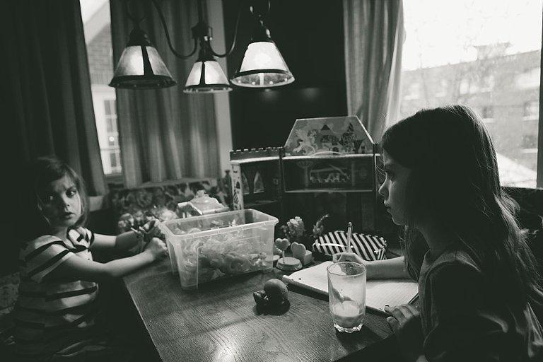 little girls do homework at dinner table - family documentary photography