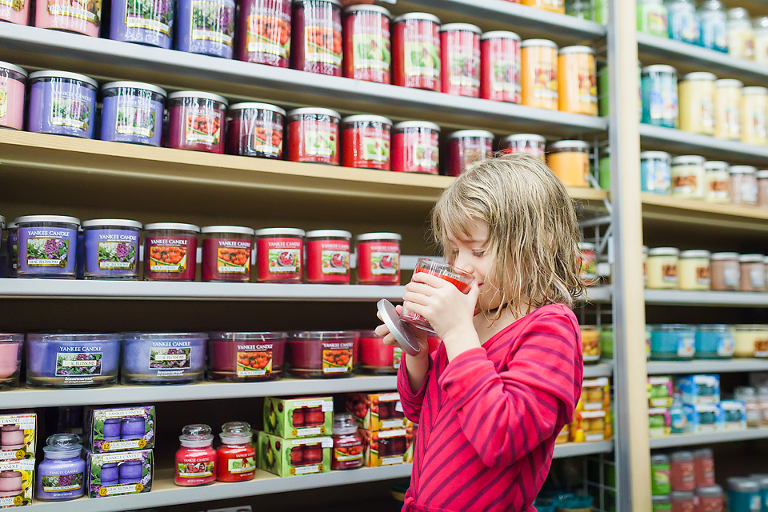 little girl sniffs scented candles - family documentary photography
