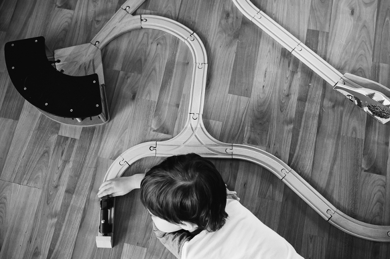 black and white little boy with train set - family documentary photography