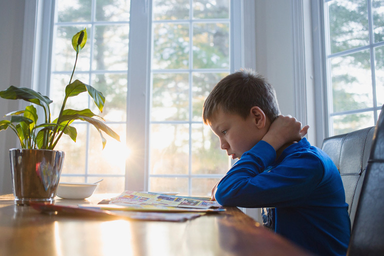 little boy reads at kitchen table - family documentary photography