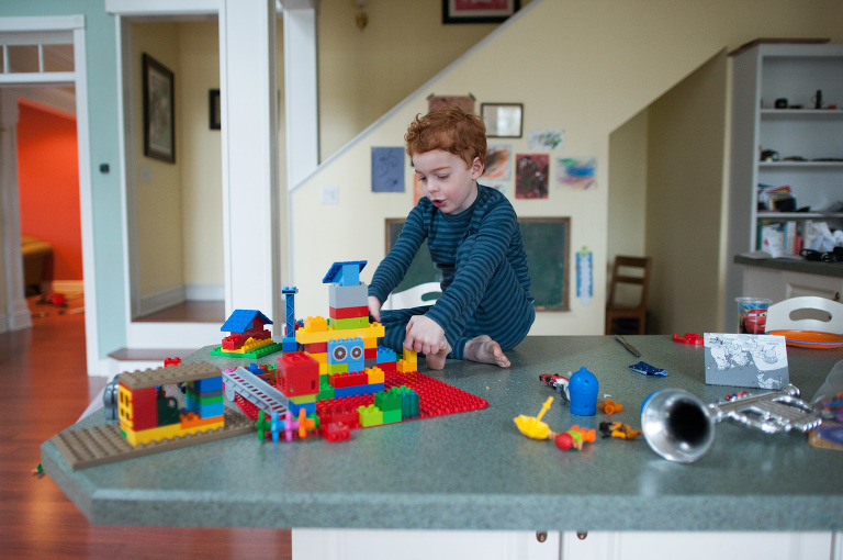 Little boy plays with Legos on counter - family documentary photography