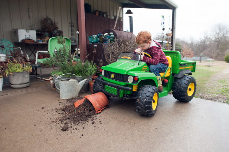 Family Documentary Photography - Little boy runs over planter in John Deere