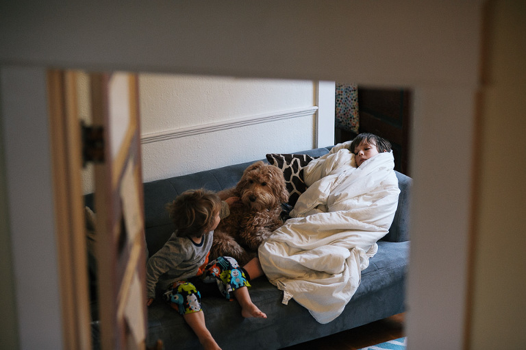 boy wrapped in blanket on couch with brother - family documentary photography