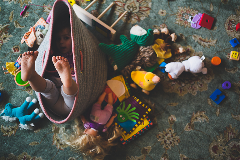 child hides in toy basket - family documentary photography