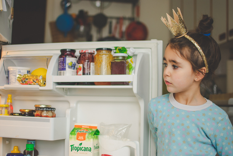 girl with crown looks in fridge - Family Documentary Photography
