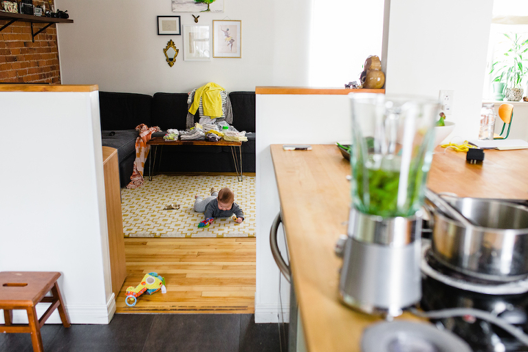 Baby cries on floor while cooking - Elisabeth Simard Photographie - Perfectly Real Artist