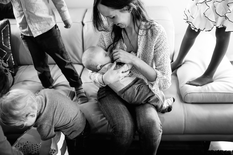 mom loves on baby while childred play around her - Elisabeth Simard Photographie - Perfectly Real Artist
