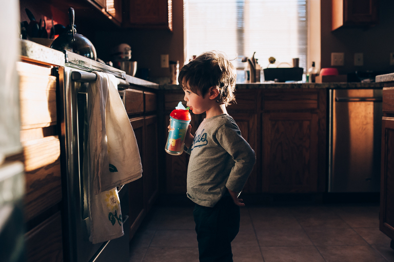 LIttle Boy with Sippy cup gazes at oven - Family Documentary Photography
