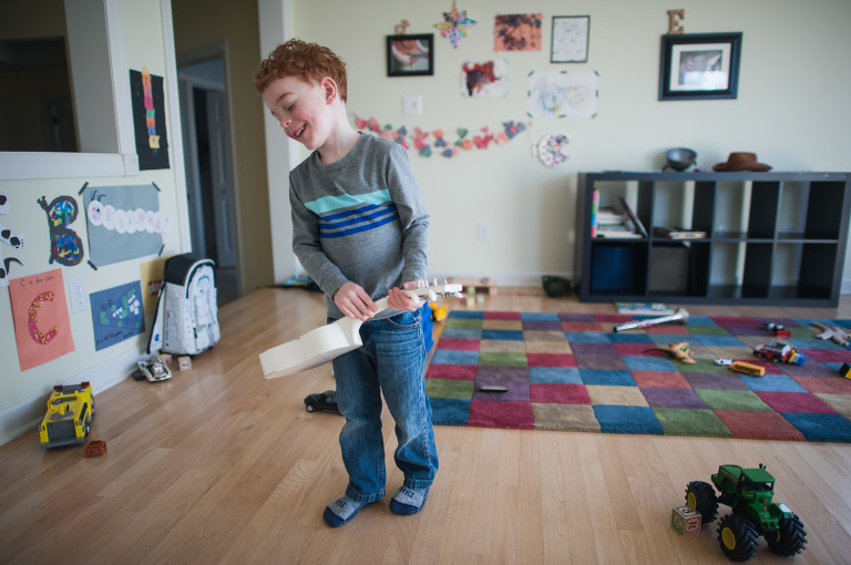 little boy in playroom with ukelele - Family Documentary Photography
