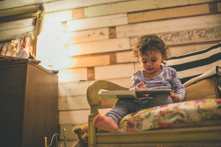 baby reads by lamp light - Family Documentary Photography