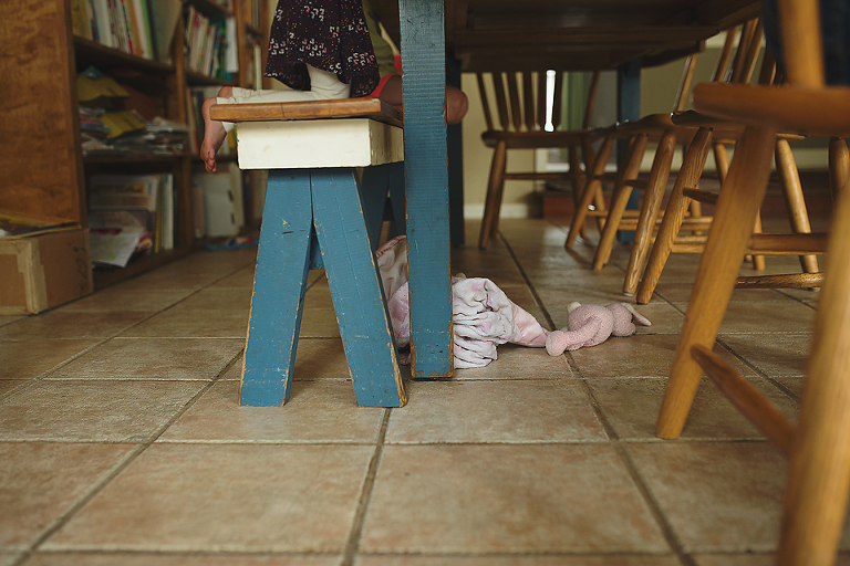 girl at table, lovey on ground - Family Documentary Photography