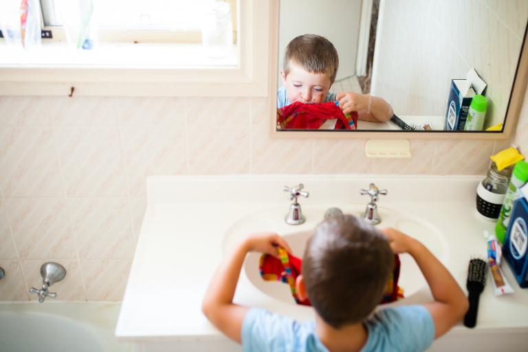 little boy washes face - family documentary photography