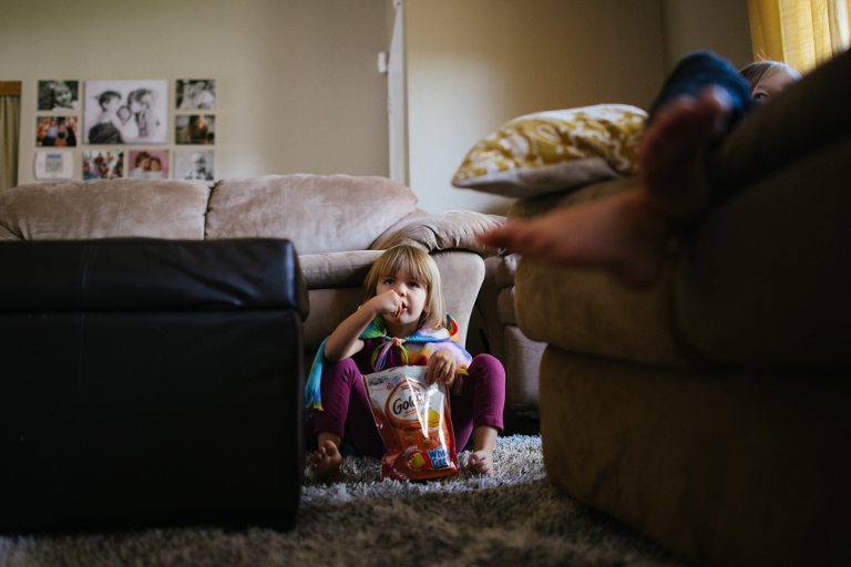 little girl eats snack while watching TV - family documentary photography