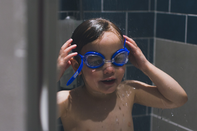 child with goggles in shower - Family Documentary Photography