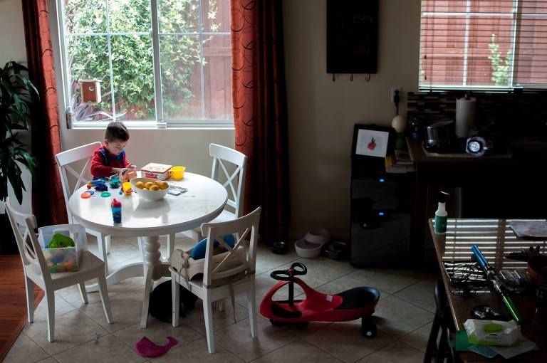 Boy plays with toys at breakfast table - Family Documentary Photography