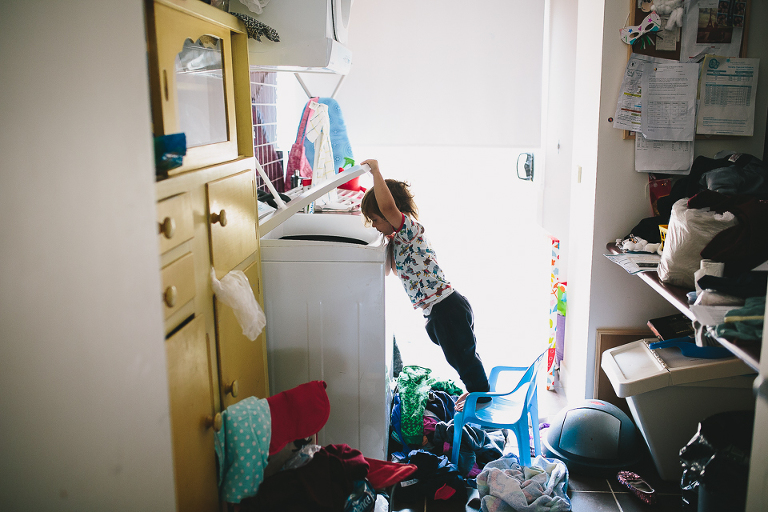 Child looks in dryer - Family Documentary Photography