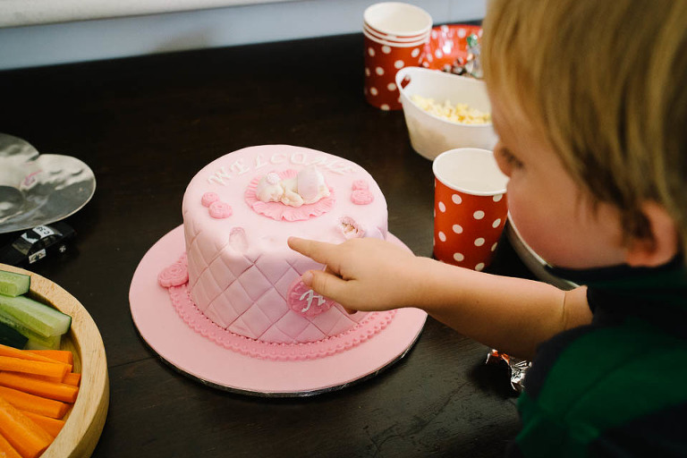 sneaking icing from cake - family documentary photography
