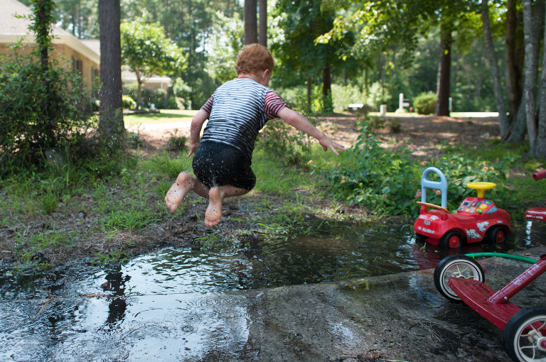Boy jumping in puddle - Family Documentary Photography Interview
