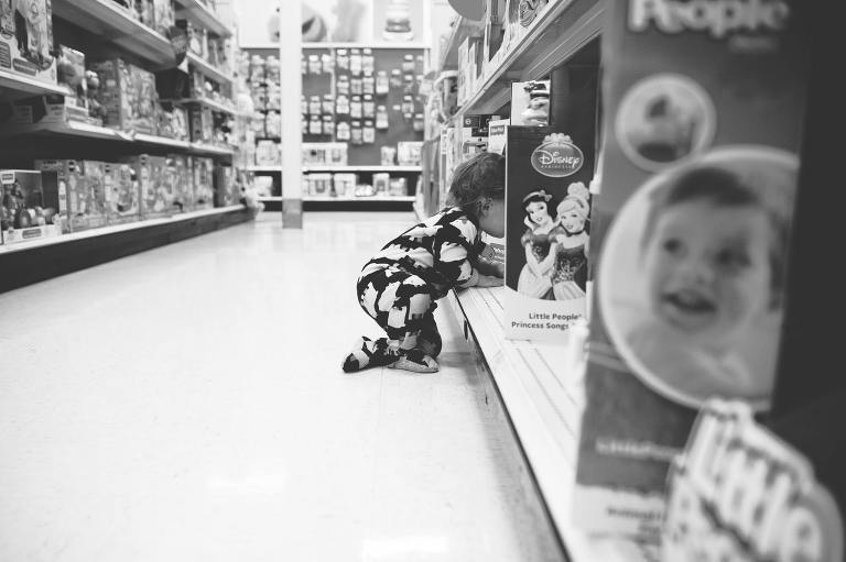boy climbing into shelf in toy aisle - at the store, family documentary photography