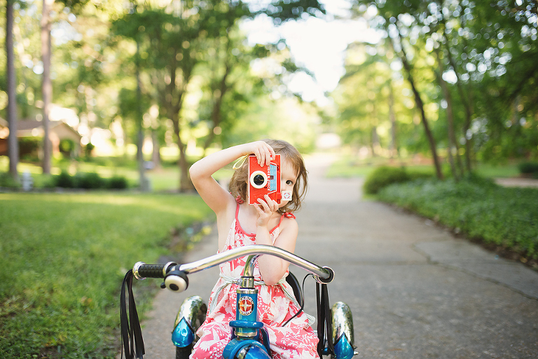 Girl on tricycle with camera - Family Documentary Photography