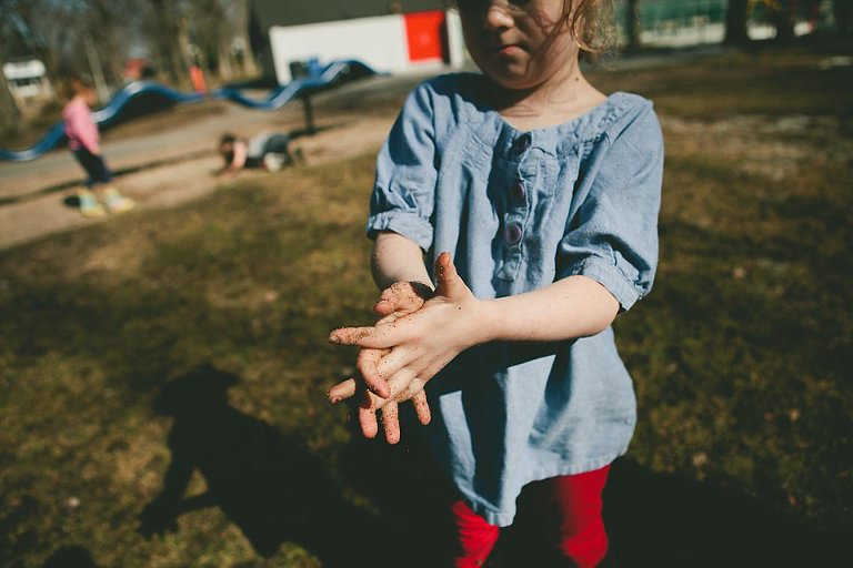Girl rubbing dirt from hands - Family Documentary Photography