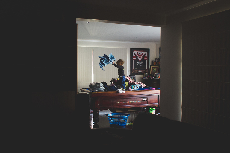 Child throwing laundry on table - Family Documentary Photography