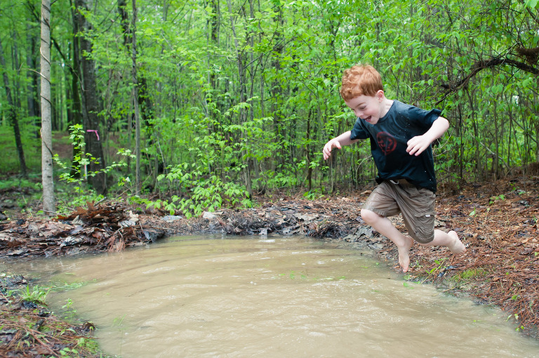 Boy jumps in puddle - Family Documentary Photography