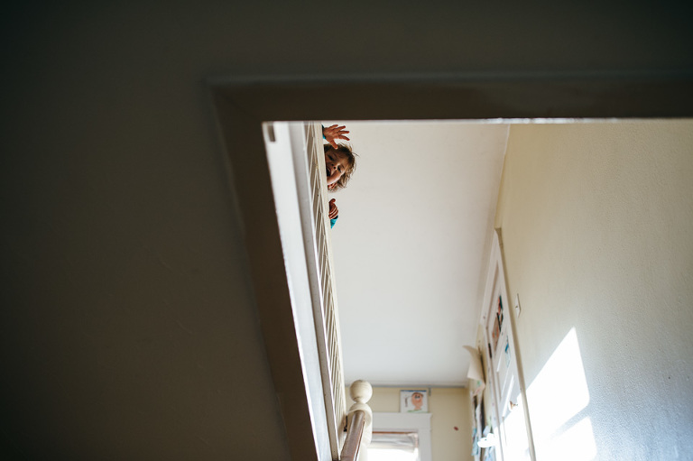boy waving from top of stairs - Family documentary photography