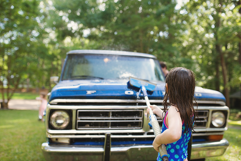 Girl washing old blue truck - Family Documentary Photography