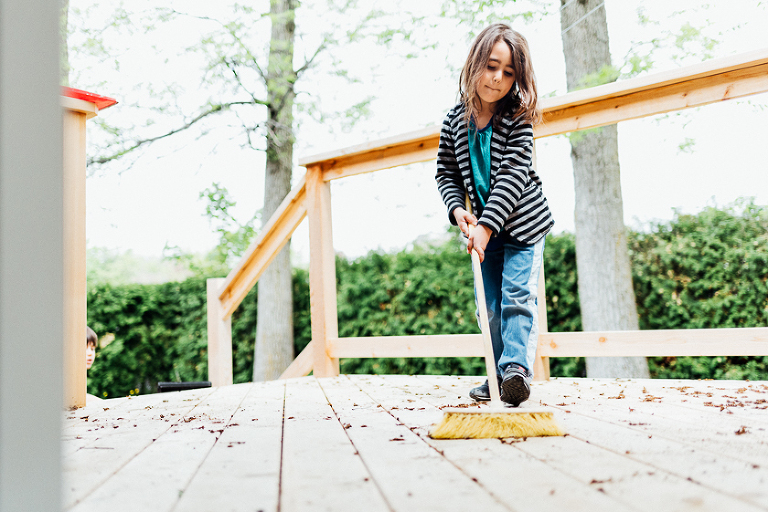 girl sweeping leaves on porch - Family Documentary Photography