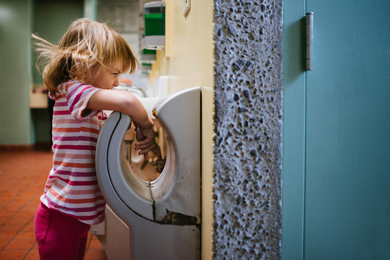 kid with hair blowing at hand dryer - Family Documentary Photography