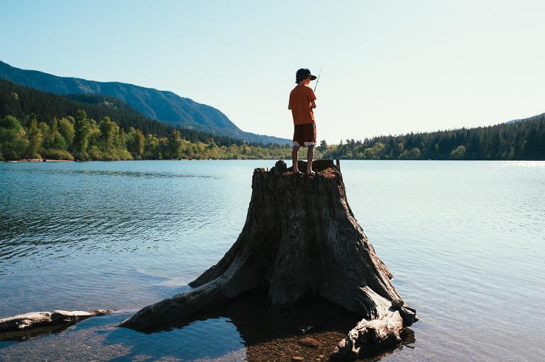 boy on tree stump in lake - Family Documentary Photography