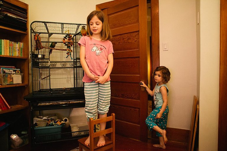 girl standing on chair with girl in doorway - Family Documentary Photography