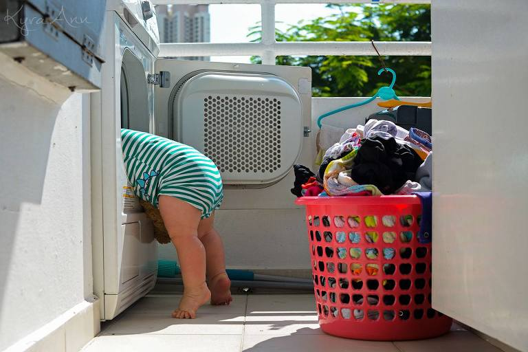 Baby leaning in dryer with basket of clothes