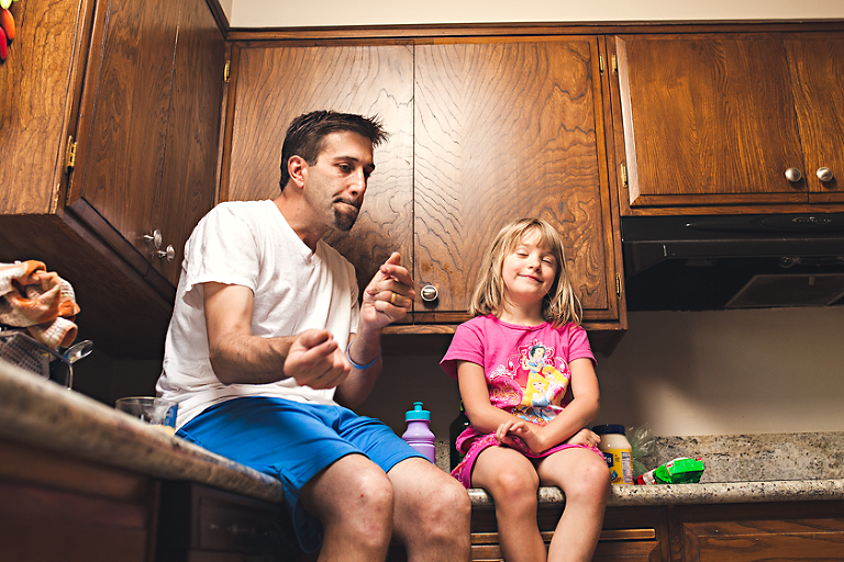 father and daughter on counter - Family Documentary Photography