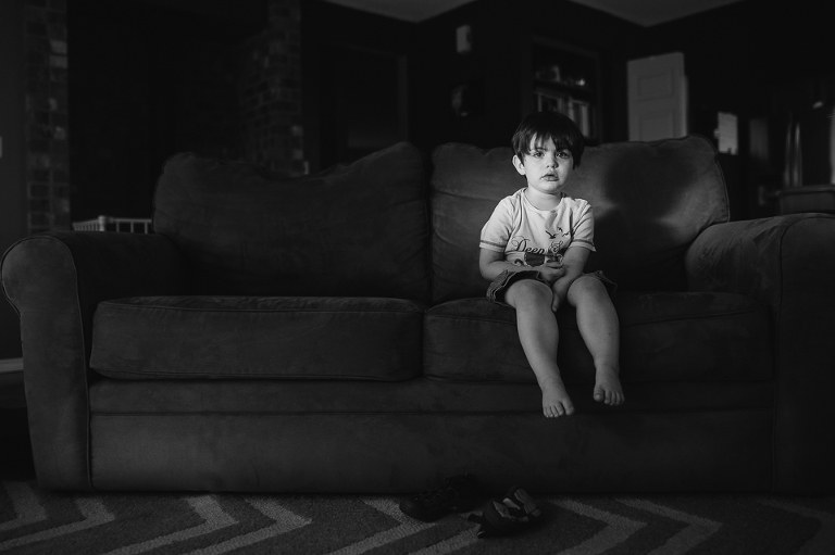 child in spot of light on couch