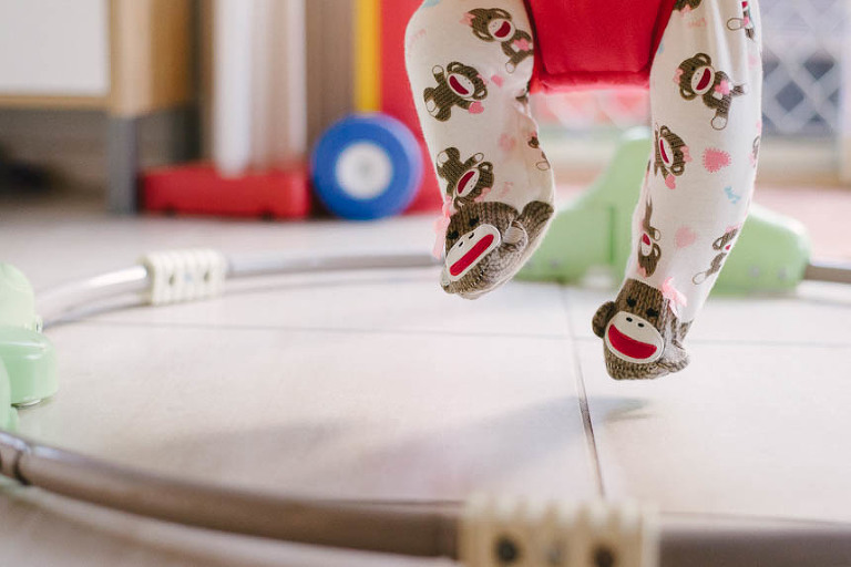 Baby feet in monkey pajamas in bouncer
