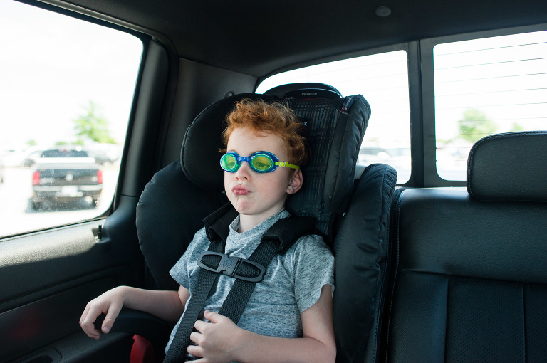 boy with goggles in car seat