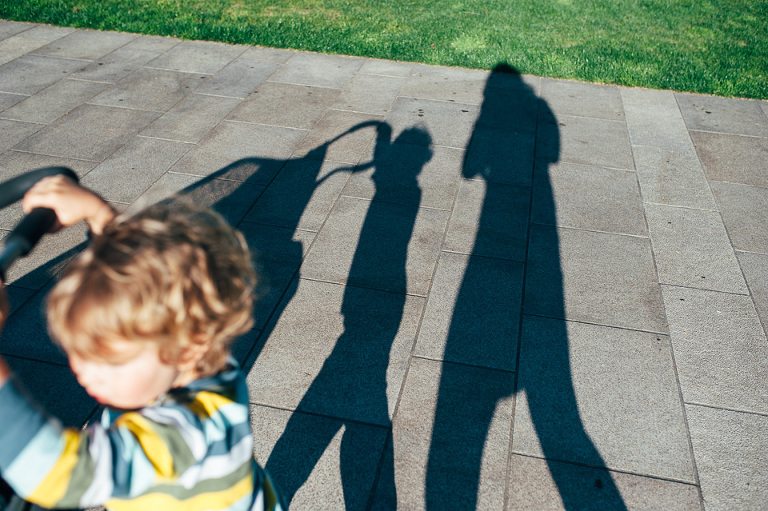 boy pushing stroller in shadow - Family Documentary Photography