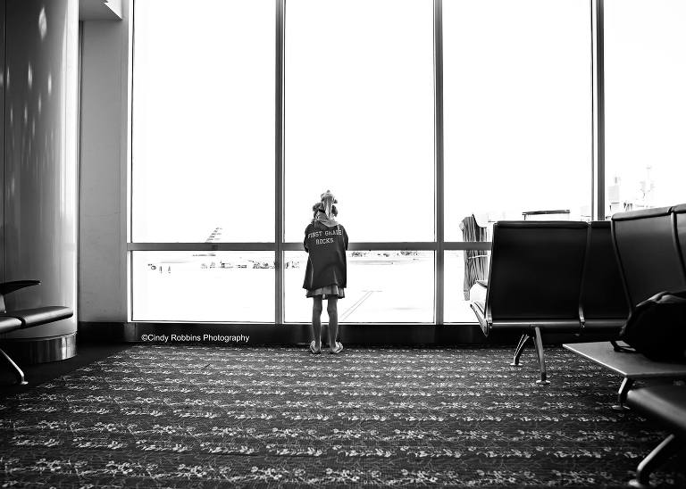child at airport window - family documentary photography On the go