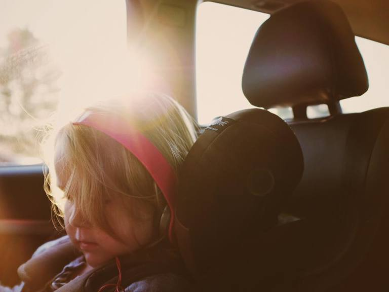 girl in carseat with sun flare - family documentary photography On the go