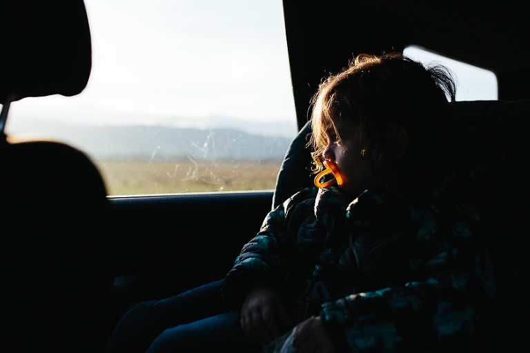 boy with pacifier looking out car window