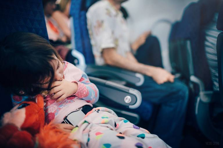 girl sleeping on plane - family documentary photography On the go