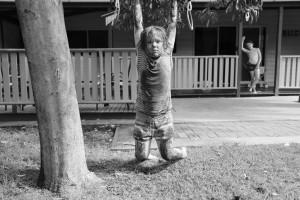 muddy girl hangs on tree limb