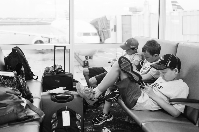 Kids waiting at airport - on the go; family documentary photography
