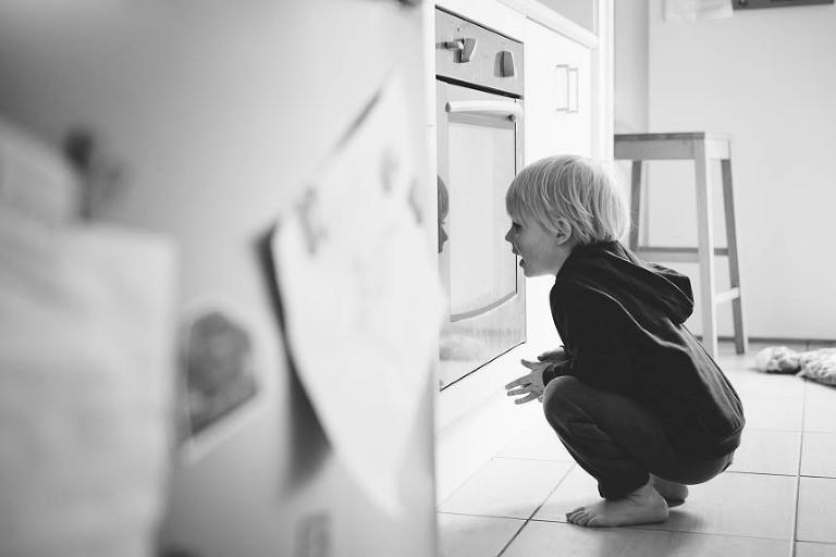 boy peering in oven