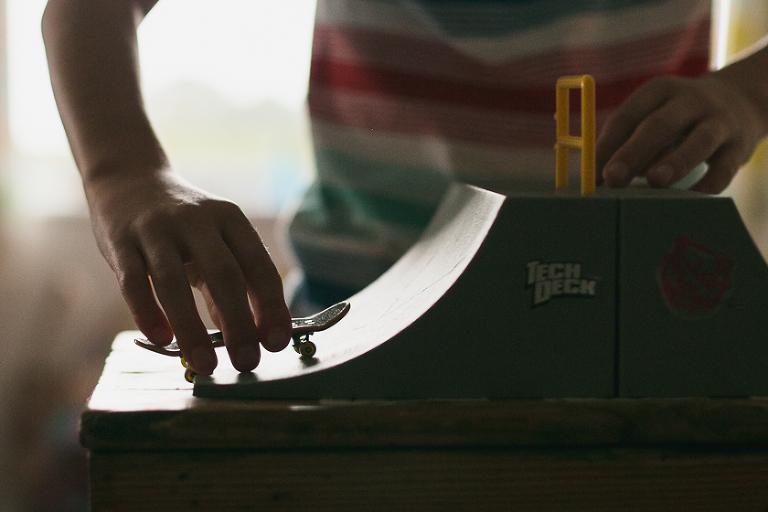 child with mini skateboard - documentary family photography