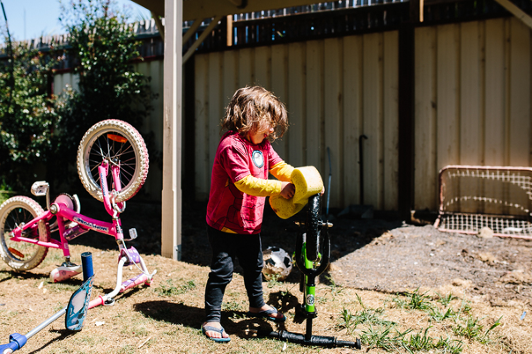 boy cleaning bike - documentary family photography