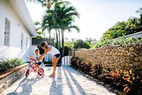 mom helps child on bike in sunshine