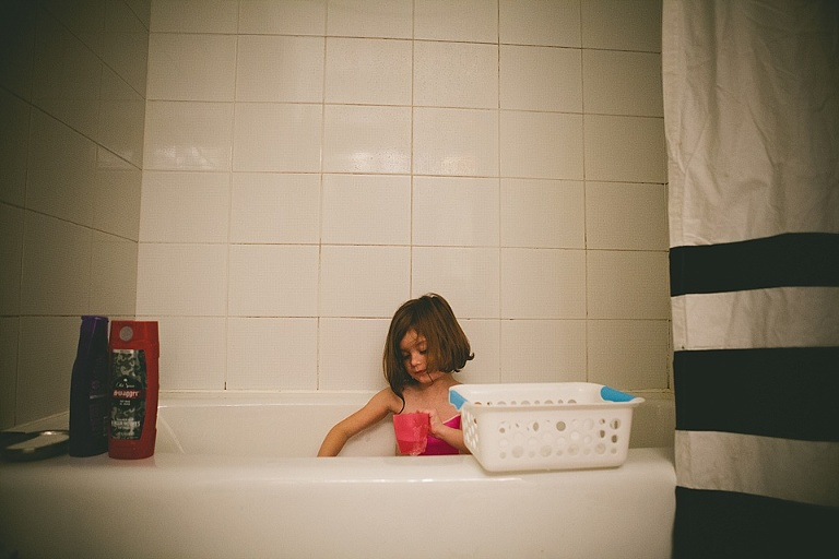 girl plays quietly in tub - Family Documentary Photography